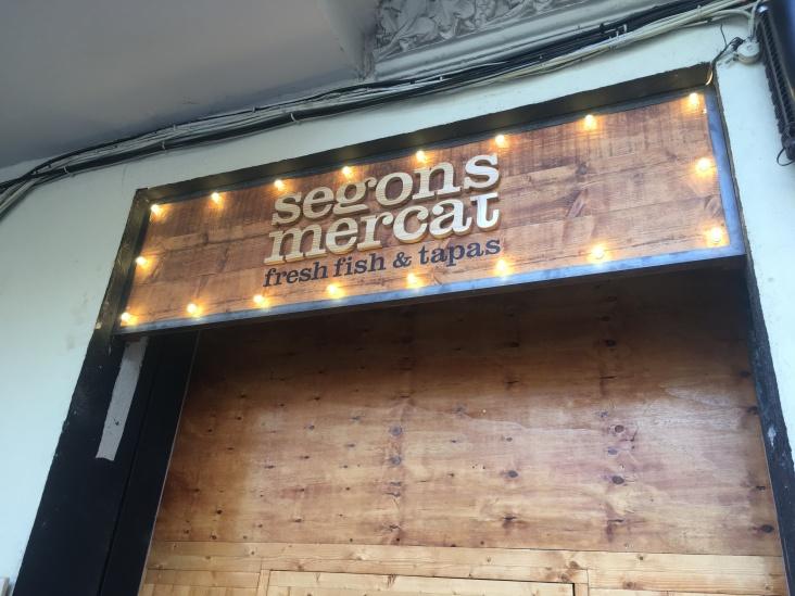 Restaurante #Segonsmercat Rótulo Vintage fabricado en madera sobre marco metálico con letras corpóreas y con iluminación de bombillas de luz.